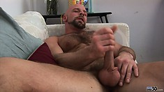Lying on the couch, he fingers his ass and strokes his cock with excitement
