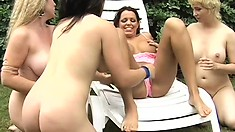 Mature lesbian gets catered to by three younger babes as they eat, toy, and finger cunts