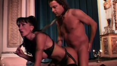 Mature brunette broad in a kinky outfit milks a younger man's cock