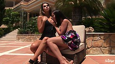 Two lovely lesbians are in the backyard doing some foreplay to get wet