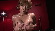 Slutty Asian babe with big glistening titties uses them on a dick